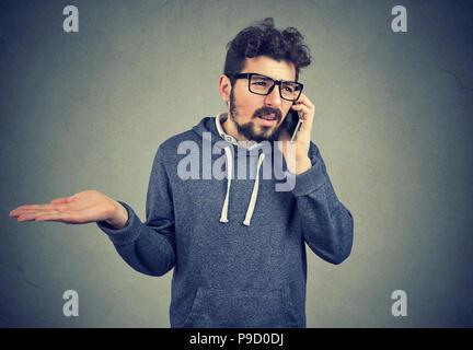 L'incompréhension et lointain appel téléphonique. Jeune homme bouleversé talking on cellphone sentiment contrarié et frustré isolé sur fond gris. Banque D'Images