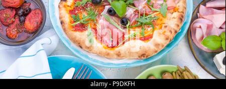 Cuisine italienne sur la table, des pizzas et des antipastis. Belle portion pour un dîner en famille. Les olives et le basilic. Fromage et Jambon Banque D'Images