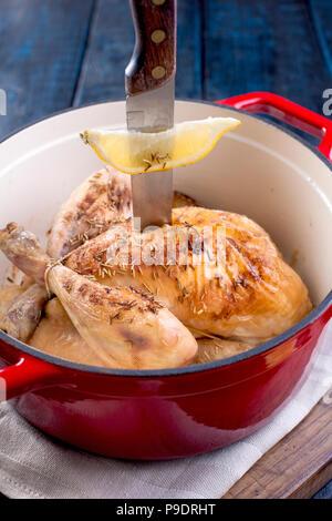 Le poulet entier cuit au four avec du citron et du romarin dans une fonte rouge. Fond en bois bleu et gris serviette. Le couteau est bloqué dans le poulet et de la fourchette. Espace libre pour le texte
