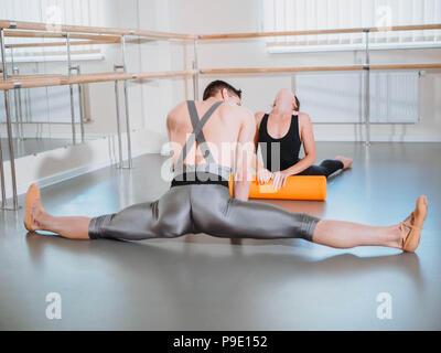 Préparation du corps avant son rendement en ballet studio. Danseur et danseuse réchauffe près de barre sur la répétition. Banque D'Images