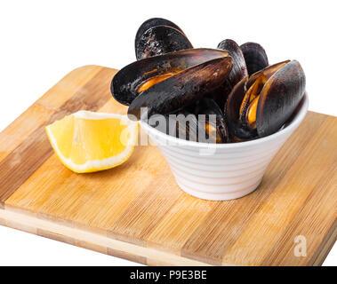 Les moules cuites dans un bol avec du citron sur planche de bois