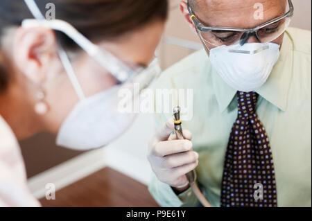 Libre d'un dentiste et son assistant travaillant sur un patient dans un cabinet dentaire. Banque D'Images