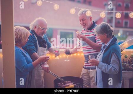 Groupe de personnes adultes senior en activité de loisirs faire un barbecue barbecue sur le toit-terrasse de la maison avec vue sur la montagne. repas et du vin pour deux hommes et deux Banque D'Images