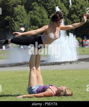 Berlin, Allemagne. 16 juillet, 2018. Deux jeunes femmes de Chicago, Illinois, n'acrobatie au Lustgarten à des températures de 27 degrés. Selon les météorologues, les températures sont destinés à rester au chaud dans les jours suivants. Credit: Wolfgang Kumm/dpa/Alamy Live News Banque D'Images