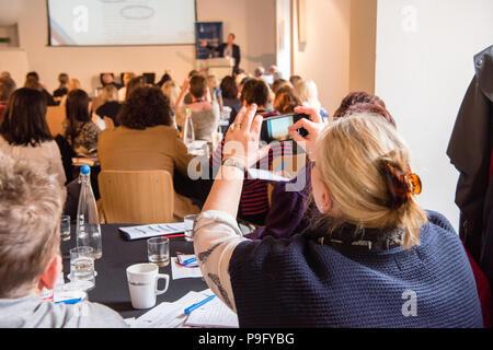 Blanc blonde femme d'âge moyen peut contenir jusqu'son smartphone pour prendre une photo d'une présentation powerpoint lors d'une conférence avec un bon nombre de personnes dans la chambre Banque D'Images