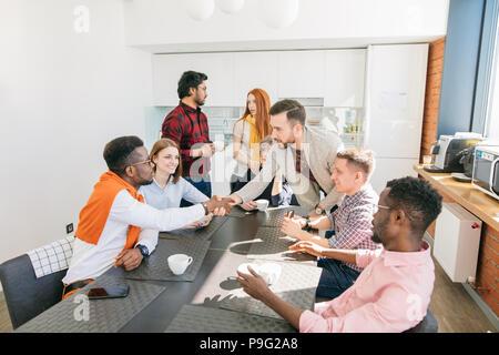 Photo en gros plan de deux business men shaking hands pause café dans la cantine moderne Banque D'Images