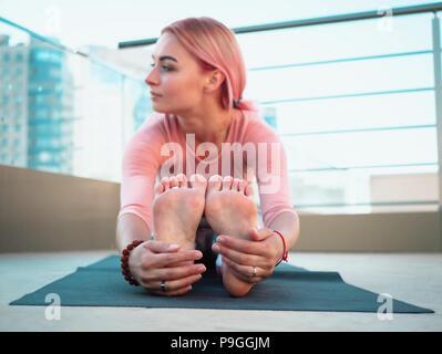 Jeune femme mince avec des cheveux teints en rose faisant du yoga pratique sur terrasse de ville moderne. Maintien de la jeune fille en bonne santé et détente sur le corps pendant la pratique sur le toit Poser Banque D'Images