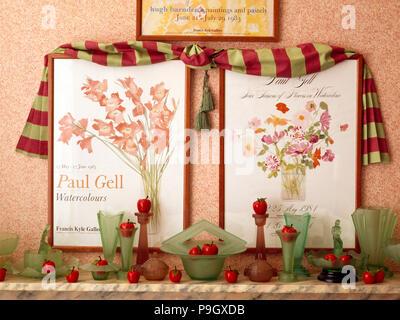 Tissu drapé et deux affiches floral au-dessus de la tablette avec collection de verrerie vintage Banque D'Images