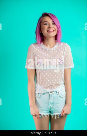 Portrait of attractive young woman with a peint les cheveux colorés, slim figure. Demi-longueur et permanent à côté. Isolé sur fond bleu. Banque D'Images