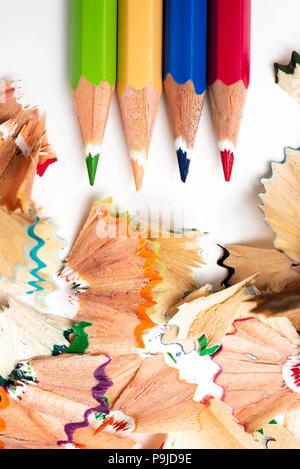 Portrait de certains des crayons de couleurs différentes et une pile de copeaux en forme d'éventail de couleurs différentes sur un fond blanc Banque D'Images