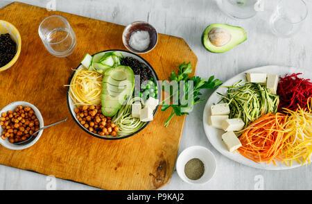 L'alimentation saine alimentation propre. Bol de renforts spiralés Bouddha avec des légumes sur une table en bois blanc, vue du dessus Banque D'Images
