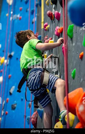 Jeune garçon grimper sur la paroi intérieure de la pratique rock gym Banque D'Images