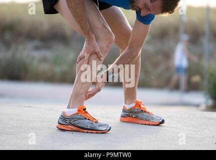 Close up de runner toucher douloureux tordu ou cassé la cheville mollet tibia ou d'un accident d'entraînement sportif runner sport running concept entorse de cheville