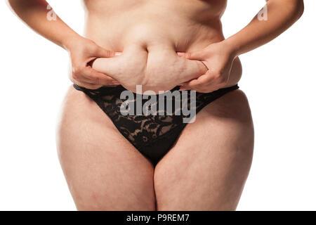Grosse femme pincer son estomac sur un fond blanc Banque D'Images