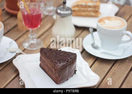 Le morceau de gâteau au chocolat sur la table de terrasse en été dans un café, pique-nique, table de jeu Banque D'Images