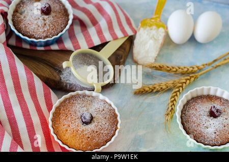 Les gâteaux avec cerries sur une table dans de petites tasses en porcelaine .Il y a des oeufs, de la farine, du blé, du sucre en poudre à côté des gâteaux. Banque D'Images