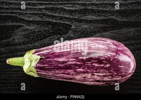 Un rayé aubergine pourpre Vue de dessus isolé sur fond de bois noir Banque D'Images