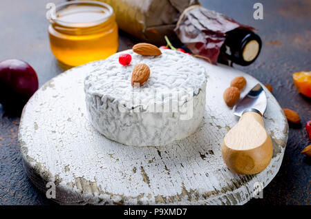 Tête ronde de fromage bleu avec du miel, de cassis, de fruits à coque et une bouteille de vin sur un tableau sombre, concept de gastronomie, fromage italien, romantique ev Banque D'Images