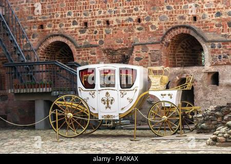 Vieux blanc 848 avec jantes dorées, debout dans la cour intérieure de l'ancien château contre le mur de brique rouge. Banque D'Images