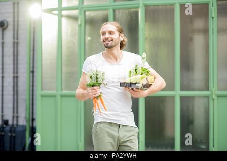 Man carrying boîte pleine de légumes crus frais vient d'acheter au marché local en plein air sur le fond vert Banque D'Images