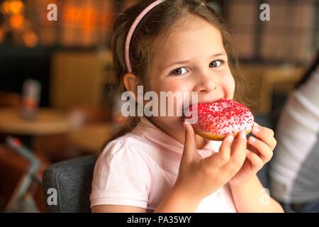 Happy girl eating feuilletée dans un café. Les mets sucrés. Les tendances de l'alimentation. Copy space Banque D'Images