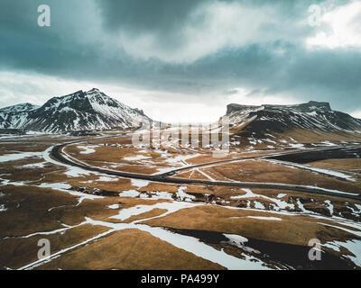 L'Islande vue aérienne paysage avec la neige et les nuages, et de la rue de l'herbe verte et jaune Banque D'Images