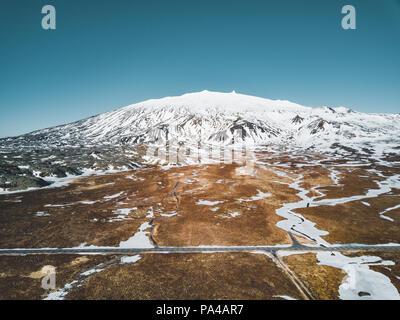 Photo d'un drone aérien vide quitter road route vers une énorme montagne volcanique Snaefellsjokull au loin, près de Snaefellsjokull parc national, de l'Islande. Banque D'Images