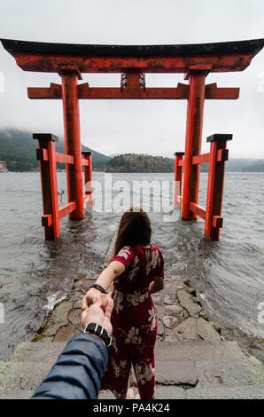 Portrait de jolies femmes tenant la main de son petit ami tout en le menant à un grand torii de Hakone Shrine construit sur le Lac Ashi. Couple dans l'amour. Banque D'Images