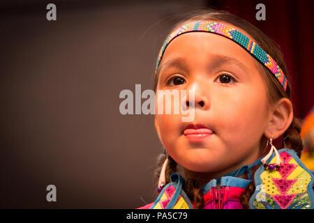 Close up portrait of Little Native American girl habillé en bandeau coloré, d'oreille et à la robe de l'avant avec la langue entre les lèvres. Banque D'Images