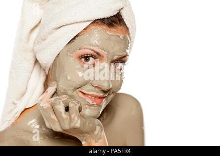 Jeune femme positive avec l'argile verte masque sur son visage Banque D'Images