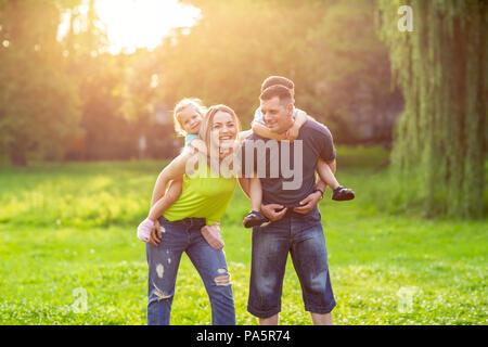-Les parents de ferroutage de la famille jouant avec leurs enfants dans le parc Banque D'Images
