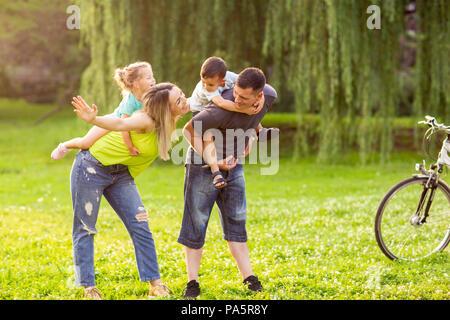 - Ferroutage famille Smiling young parents jouer avec leurs enfants dans le parc Banque D'Images