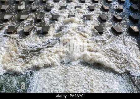 Flux puissant d'eau moussante se bloque sur des pierres en béton-jetées près du barrage. Banque D'Images