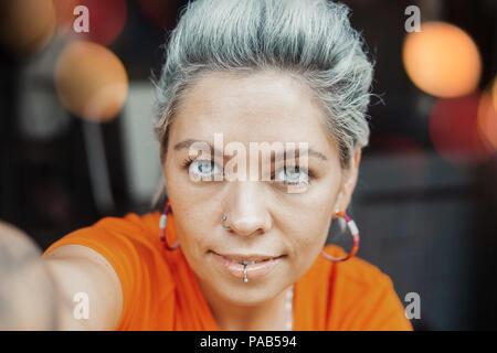Belle fille blonde pensive en tee-shirt orange de décisions au café selfies Banque D'Images