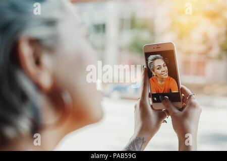 Belle fille blonde en T-shirt orange de décisions au café selfies par son téléphone Banque D'Images