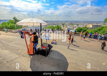 Paris, France - le 3 juillet 2017: skyline au-dessus de Paris et de l'harmoniciste sur les marches du Sacré Cœur de Montmartre. Sacré-Cœur est un monument touristique populaire. Artiste de rue, jouant d'un instrument acoustique. Banque D'Images