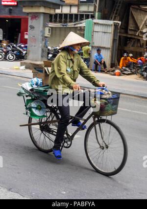 Une Vietnamienne portant un chapeau conique de paille équitation son vélo dans une rue à Ho Chi Minh City, Vietnam. Banque D'Images