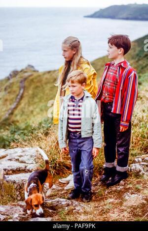 1960 enfants en groupe familial de fille et deux garçons avec animal chien beagle debout sur sentier littoral cornouaillais ci-dessus, Cornwall, England, UK. La conversion numérique des photos prises en 1968 Banque D'Images