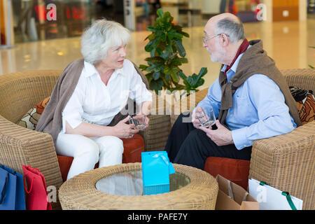Couple de personnes âgées dans le café assis, sourire et parler à l'autre Banque D'Images