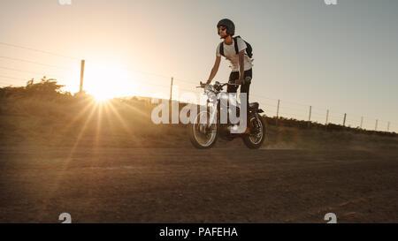 Biker debout sur sa moto en roulant par l'intermédiaire de route de campagne. Jeune homme riding hors route à vélo vintage. Banque D'Images