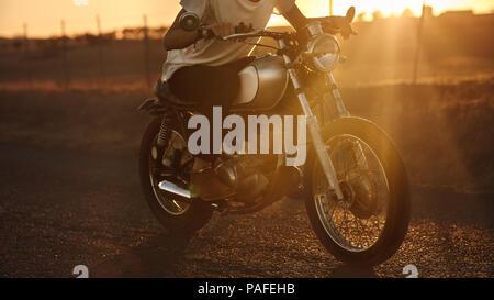 Cropped shot of male biker riding vite sur son vélo. Homme conduisant une moto rapide country road. Banque D'Images