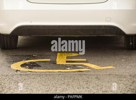 Voiture garée dans un parking handicapés bay avec mobilité logo visible sur le terrain Banque D'Images