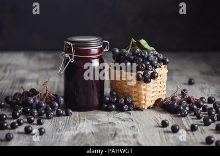 À côté de bourrage Aronia de baies fraîches. Aronia fait maison avec bol en verre de bourrage dans les baies fraîches aronia sur table en bois. Banque D'Images