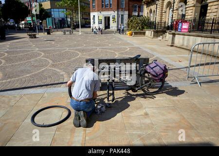 Centre-ville Blackbun dans le Lancashire, en Angleterre, l'hôtel de ville cycliste fixant un pneu crevé sur son vélo Banque D'Images