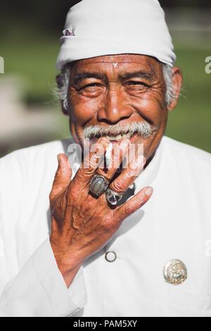 DENPASAR, INDONÉSIE - février 02, 2017: saint homme balinais avec une moustache fume et sourit en vêtements blancs traditionnels, le riz sur son front et ri Banque D'Images