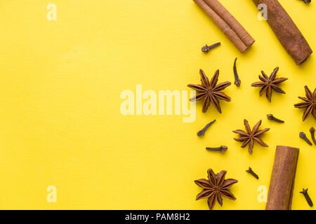 Composition de l'anis étoilé, le bâton de cannelle et de girofle sur un fond jaune. Résumé motif plat, vue du dessus. Banque D'Images