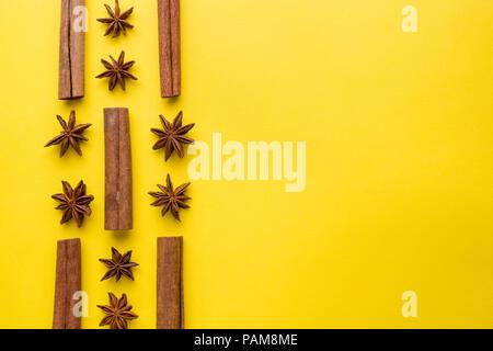 Composition de l'anis étoilé, le bâton de cannelle sur fond jaune. Résumé motif plat, vue du dessus. Banque D'Images
