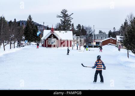 Les enfants jouer au hockey sur glace au parc à Val-David, Québec, Canada Banque D'Images