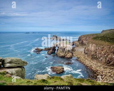 Côte Rocheuse de terres Fin, Cornwall, UK, avec l'arche, Dodnan Enys, et la formation rocheuse le chevalier armé, avec le phare de Drakkars offshor Banque D'Images