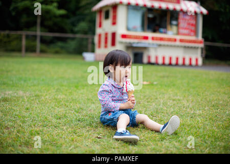 Baby Girl sitting on summer meadow et manger icecream Banque D'Images